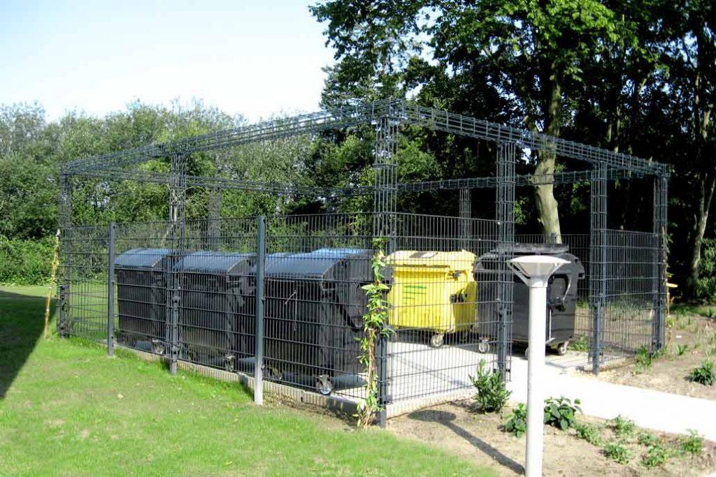Ein Mülltonnensammelplatz umgeben von einem Rankgerüst aus Stahlmatten und Rankbalken. Die frisch gepflanzten Rankpflanzen werden die Rankanlage bald begrünt haben.