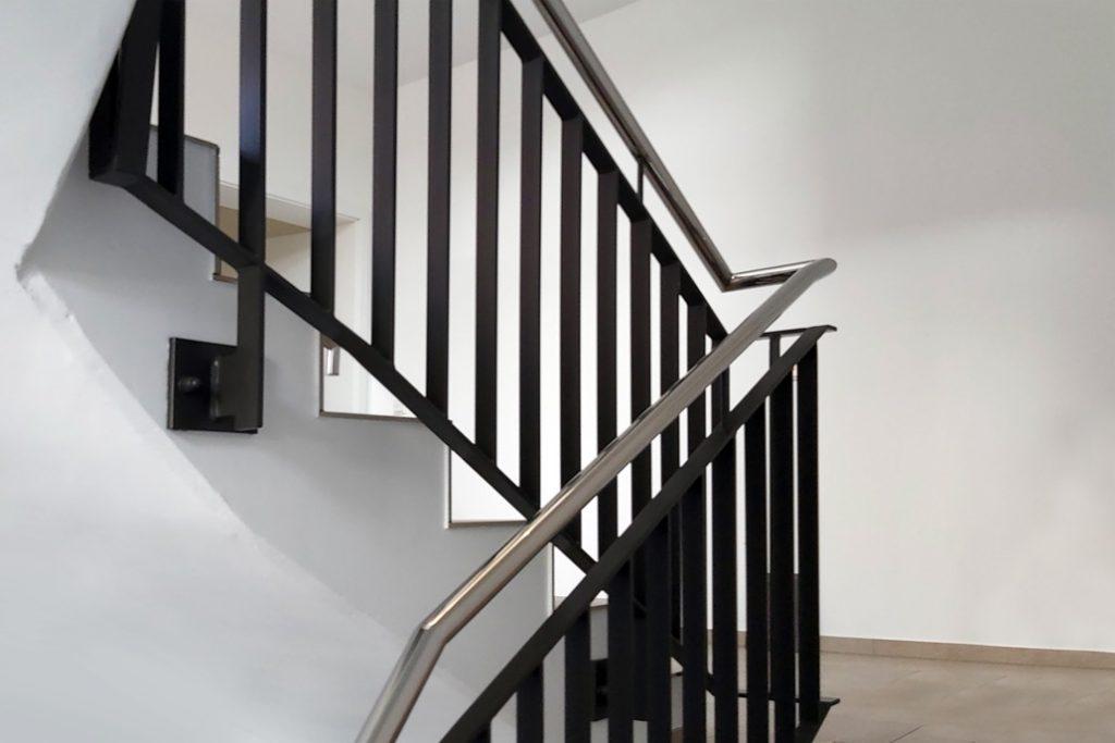 Ein Edelstahlhandlauf an einem Metallgeländer in einem Treppenhaus.