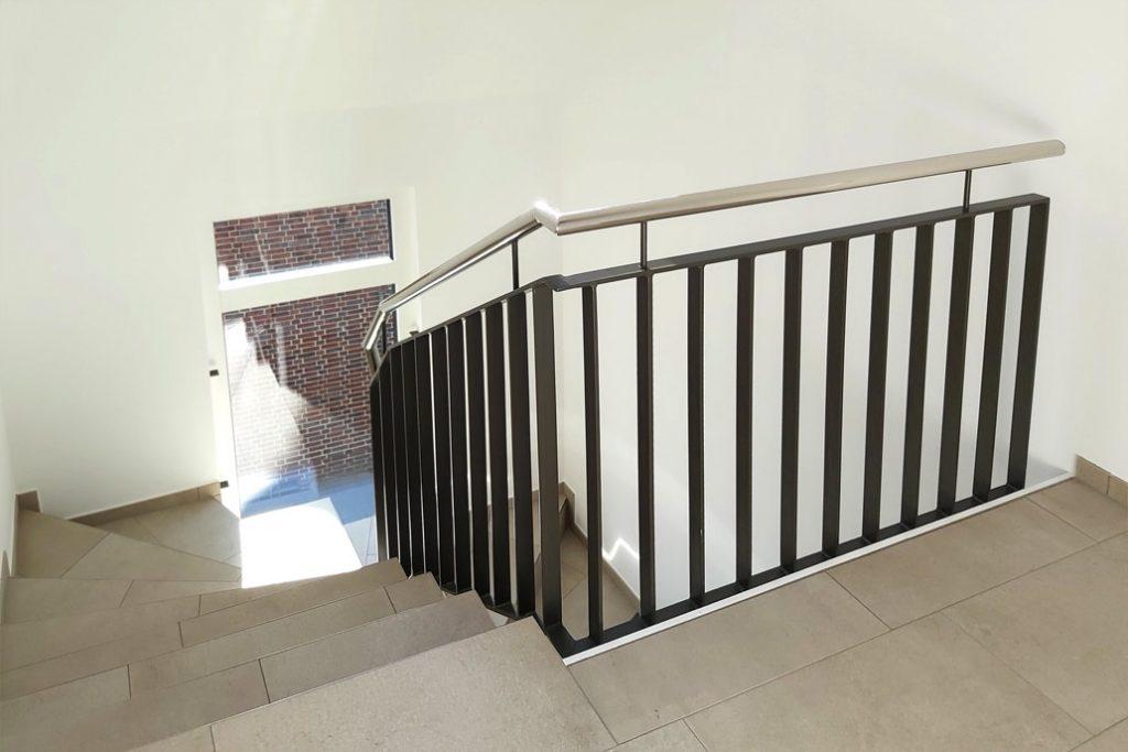 Ein Metalltreppengeländer mit einem Edelstahlhandlauf im Treppenhaus eines Mehrfamilienwohnhauses.