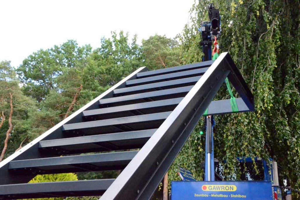 Eine Stahl-Außentreppe wird mit dem Kran unseres Unimogs angehoben und an die Hauswand gesetzt.