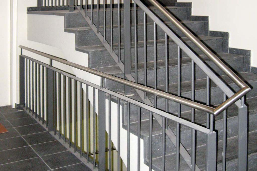 Treppengeländer aus feuerverzinbktem Stahl mit einem Edelstahl Handlauf in einem Treppenhaus. Die Füllung des Geländers besteht aus runden Stäben.