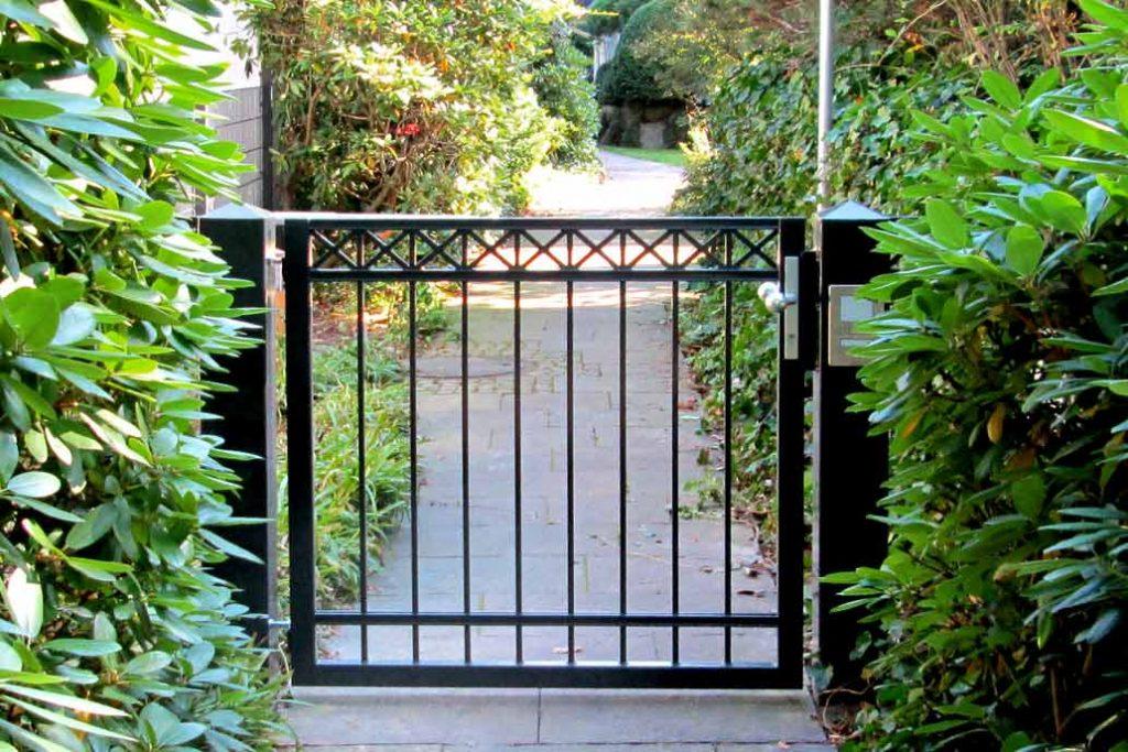 Individuelle Zauntüre / Gartentüre aus schwarz beschichtetem Stahl mit einer Stabfüllung und eingeschweißten Kreuzen.