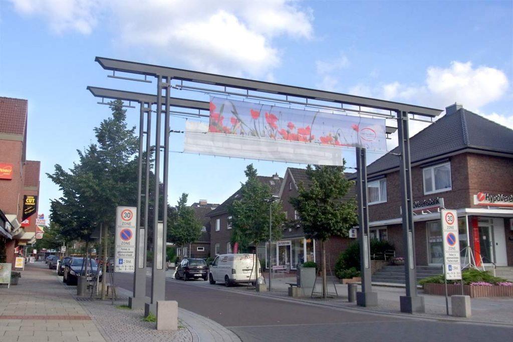 Ein großer Torbogen aus Stahl markiert den Beginn der Geschäftsstraße.