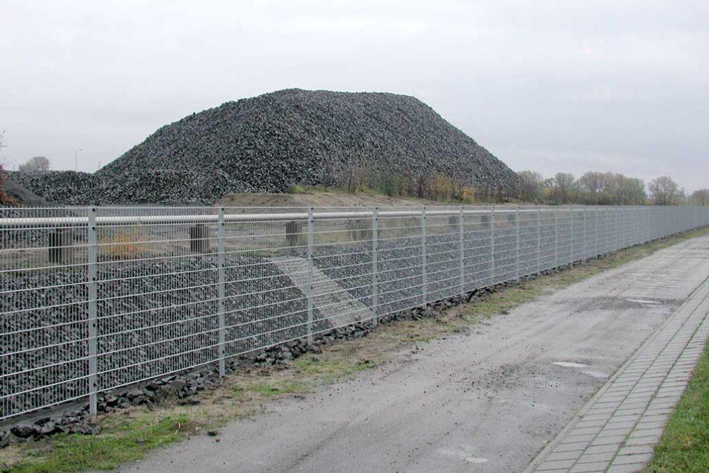Ein Stahlmattenzaun in einem Industriegebiet vor einer Halde mit Steinen.