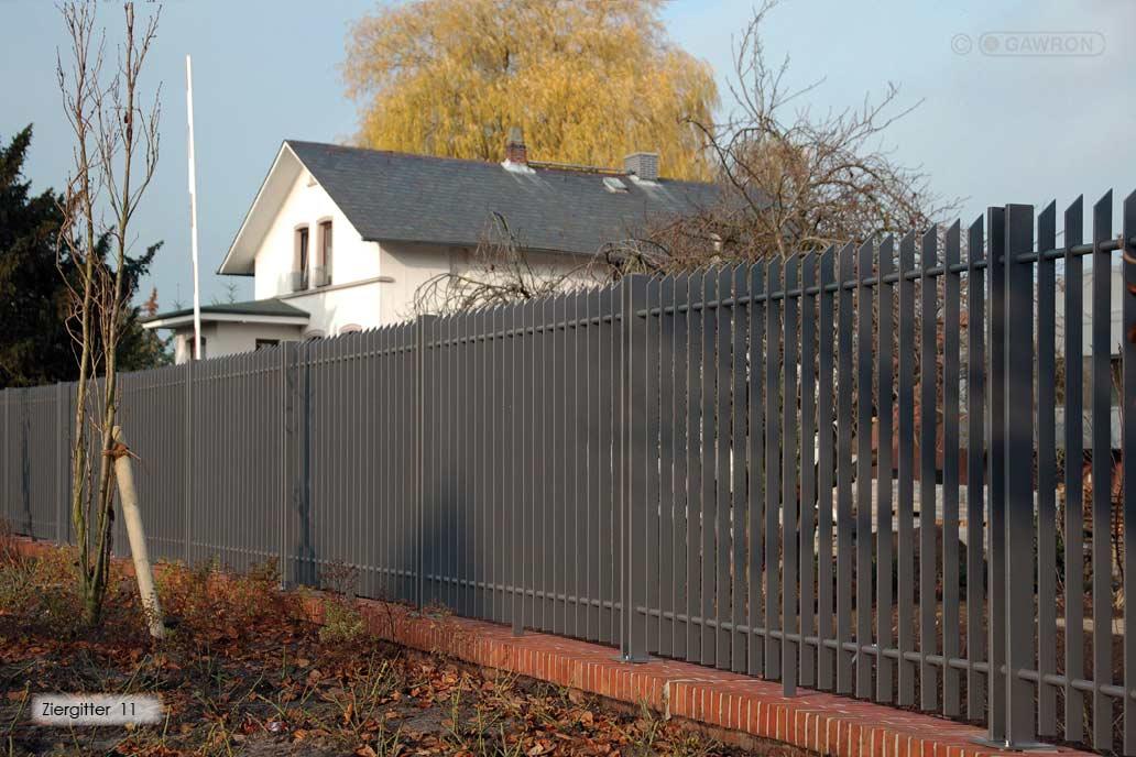 Graues Frontgitter aus Flachstahlstäben auf einer kleinen roten Ziegelsteinmauer.