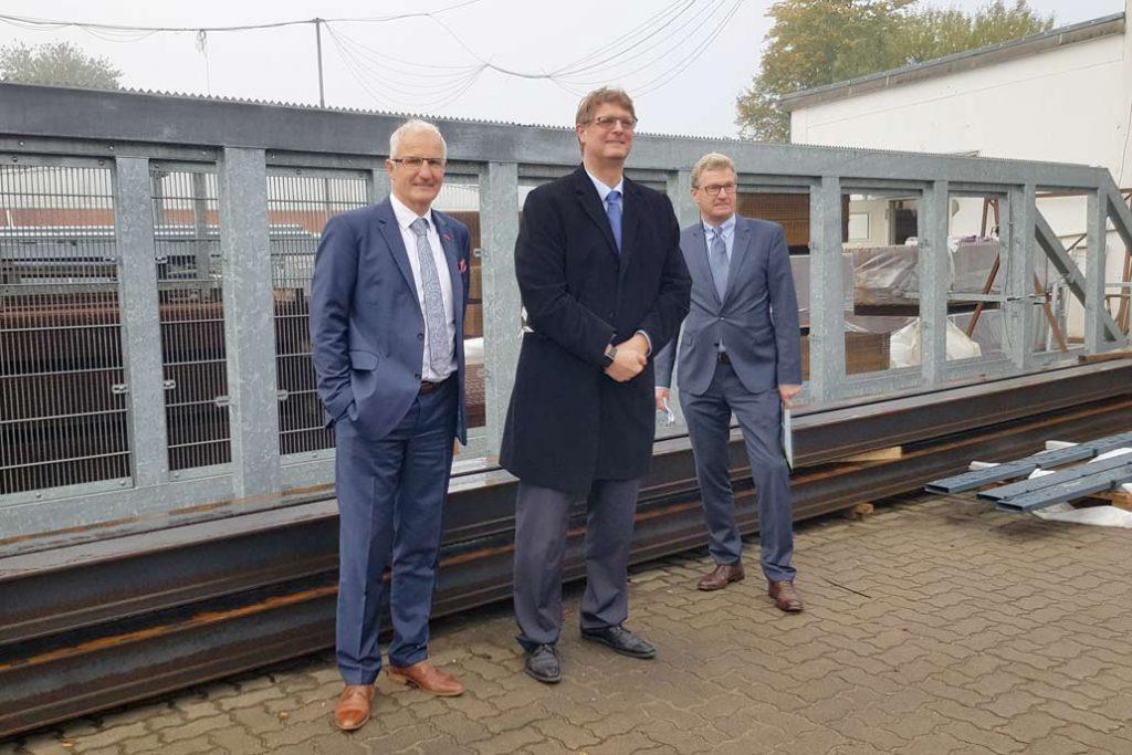 Handwerkskammerpäsident Ralf Stamer, Volker Gawron und Dr. Bernd Buchholz vor einem Schiebetor auf dem Hof von Gawron & Co in Rellingen.