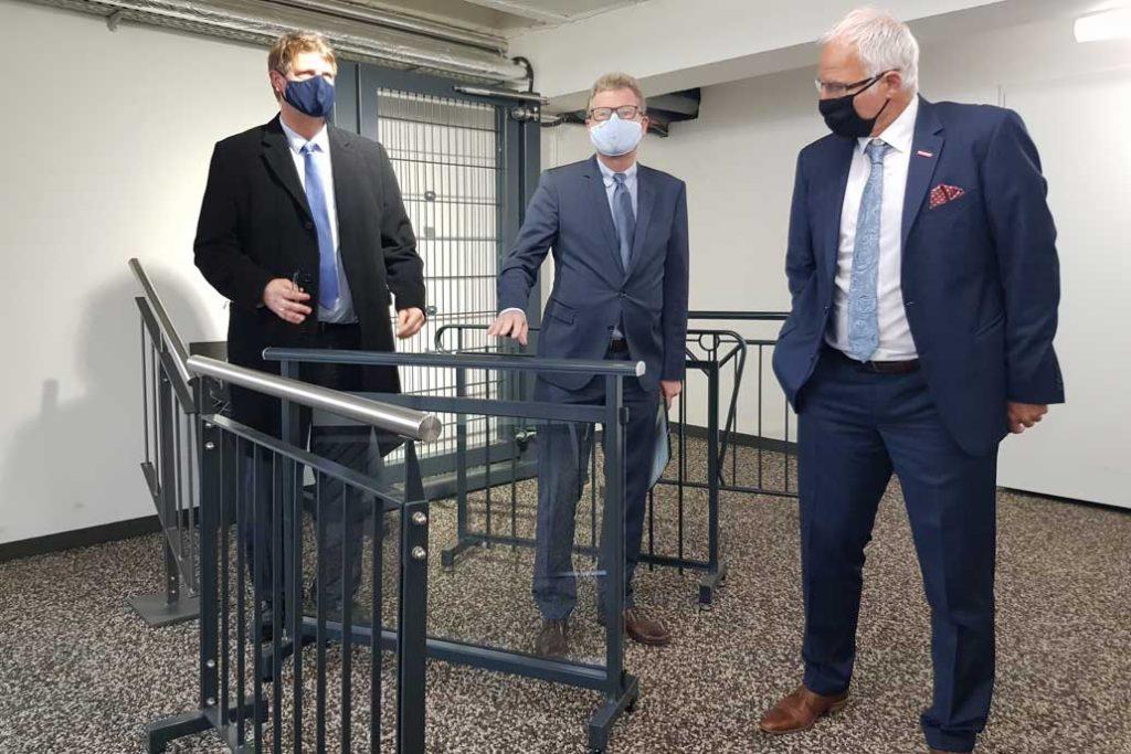 Volker Gawron zeigt Minister Dr. Bernd Buchholz und Handwerlskammerpräsident Ralf Stamer verschiedene geländer in der Ausstellung von Gawron & Co in Rellingen.