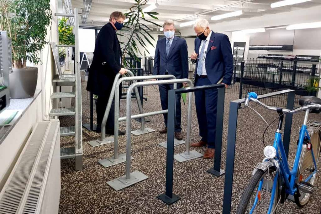 Volker Gawron, Minister Dr. Buchholz und Ralf Stamer sehen sich verschiedene Fahradbügel in der Ausstellung von Gawron & Co in Rellingen an.