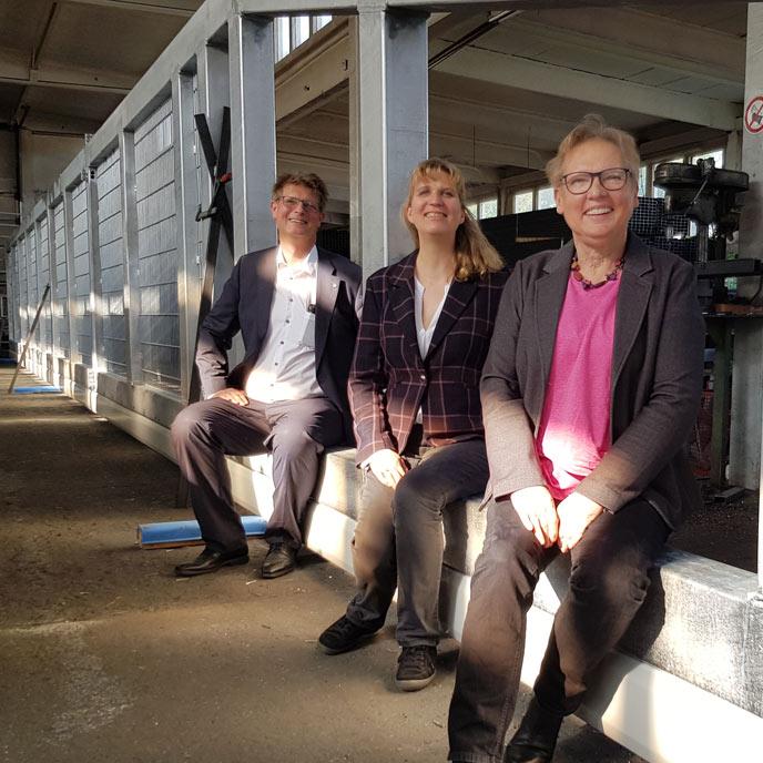 Ines Strehlau von den Grünen, Franca und Volker Gawron sitzen in einem 27 Meter langen Schiebetor gefertigt in der Produktionshalle von Gawron in Rellingen.