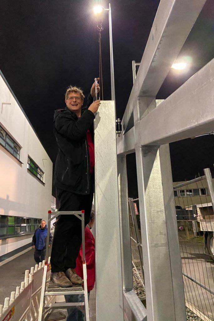 Volker Gawron steht auf einer Leiter und schraubt die Führungsrollen des 27,5 m langen, freitragenden Schiebetors fest.
