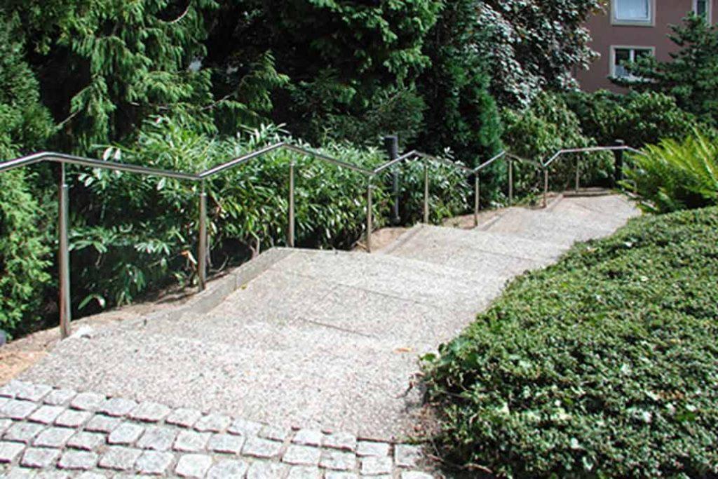 Edelstahlhandlauf an einer langen Treppenanlage in einem Park.