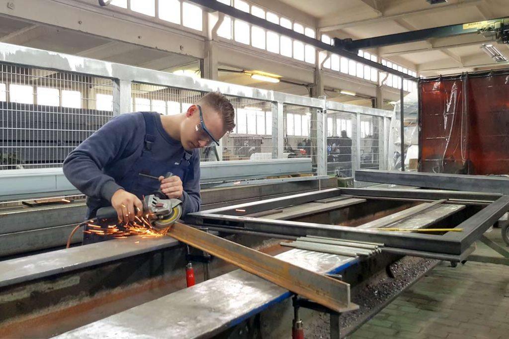 Ein Metallbau Azubi beim Flexen in der Lehrwerkstatt vo Gawron in Rellingen - probiert das auch aus im Praktikum im Metallbau Handwerk.