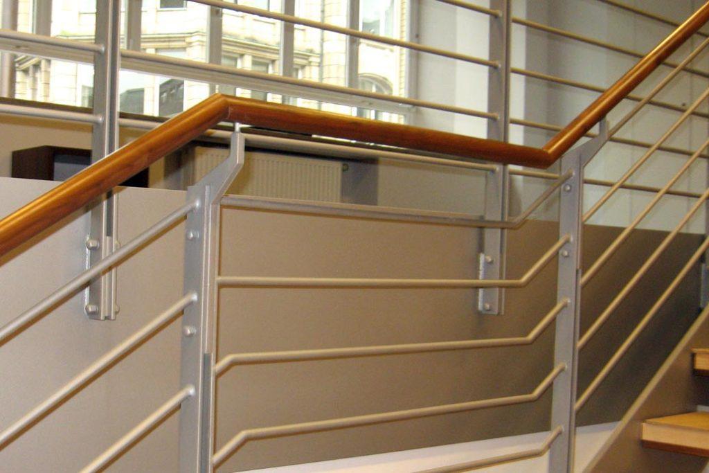 Holzhandlauf an einem Treppengländer aus Metall.