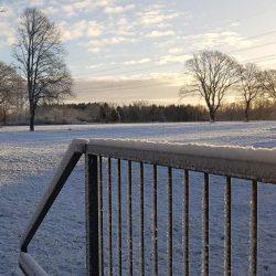 Schiebtor mit Schnee vor einem weiten schneebedeckten Feld.