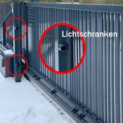 Lichtschranken an einem elektrisch angetriebenen Schiebetor im Schnee.