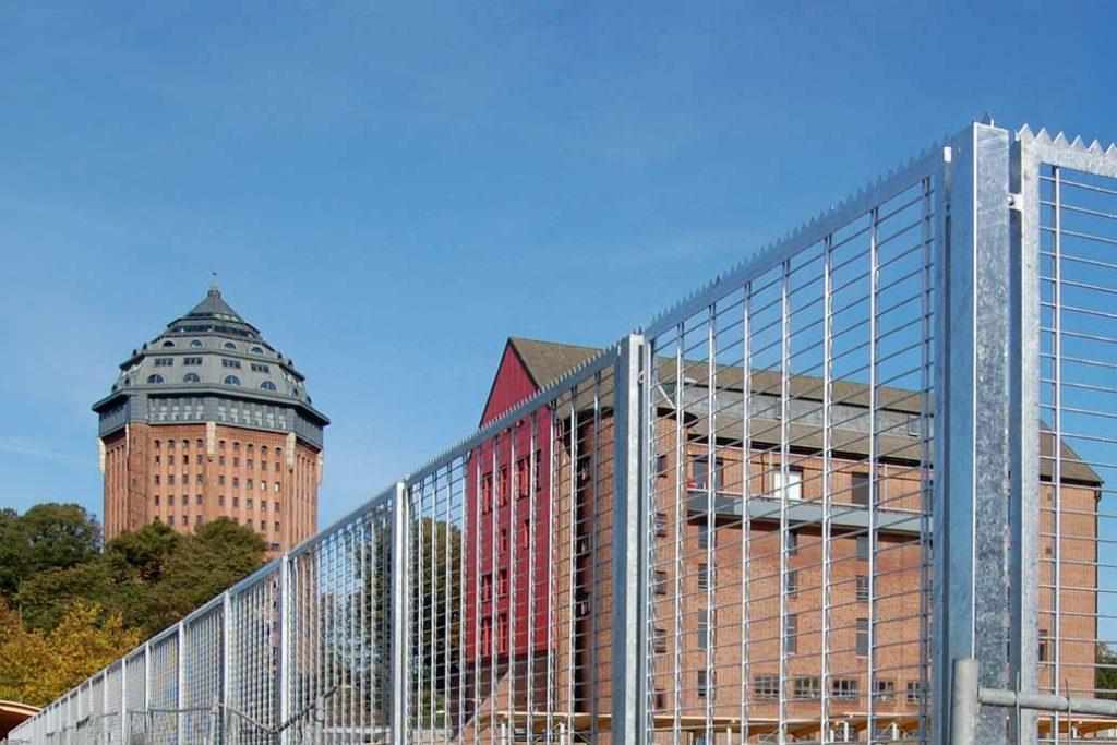 Feuerverzinkter Sicherheitszaun um das Messegelände Hamburg mit Blick zum Schanzenturm.