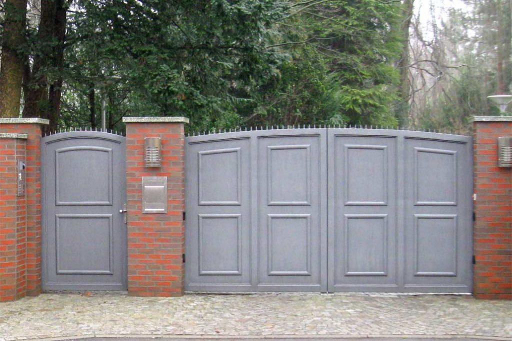 Graues blickdichtes Drehflügeltor zwischen roten Mauerpfosten. Links daneben eine Personentür.
