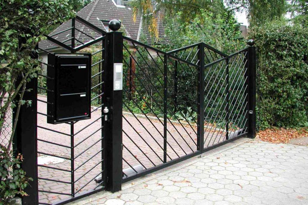 Schwarzes Drehflügeltor und Gartentür mit diagonaler Stabfüllung.