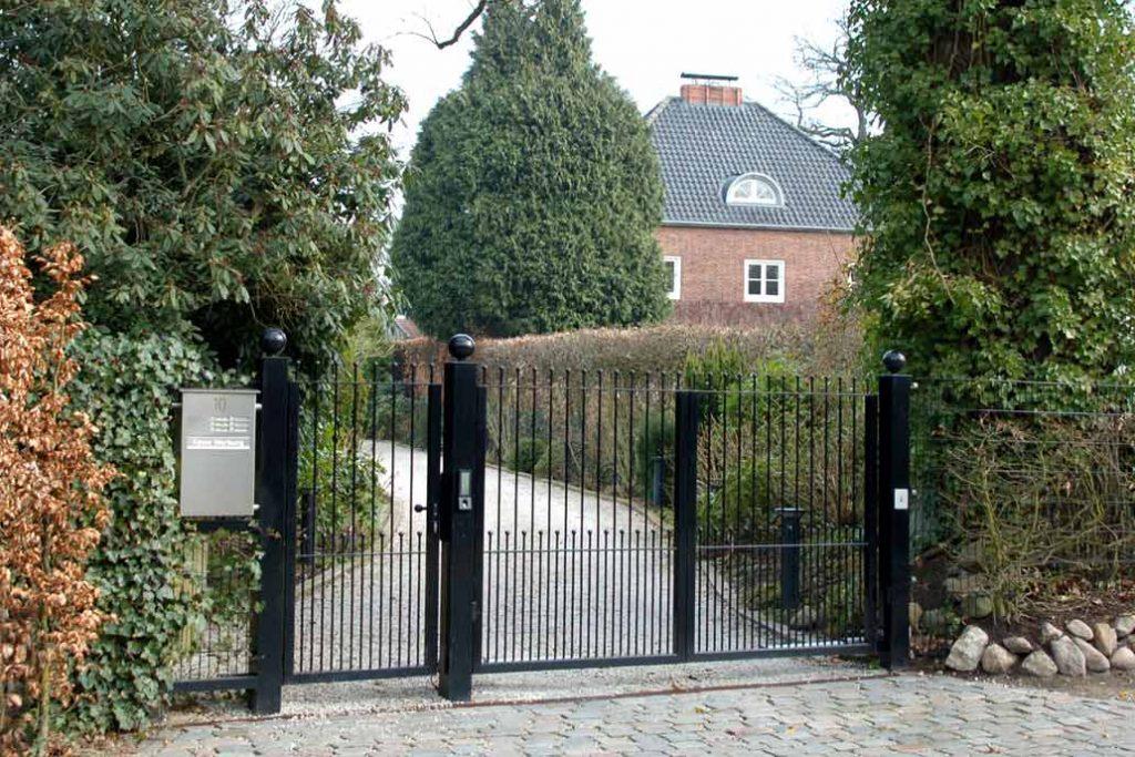 Schwarzes filigranes Drehflügeltor an einer gepflasterten Grundstückszufahrt.