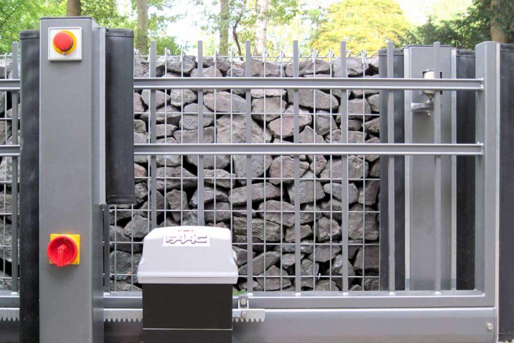 Kraftbetriebenes Schiebetor mit Sicherheitseinrichtungen Notstopp, Kontaktleisten und allpoligem Spannungstrennschalter.