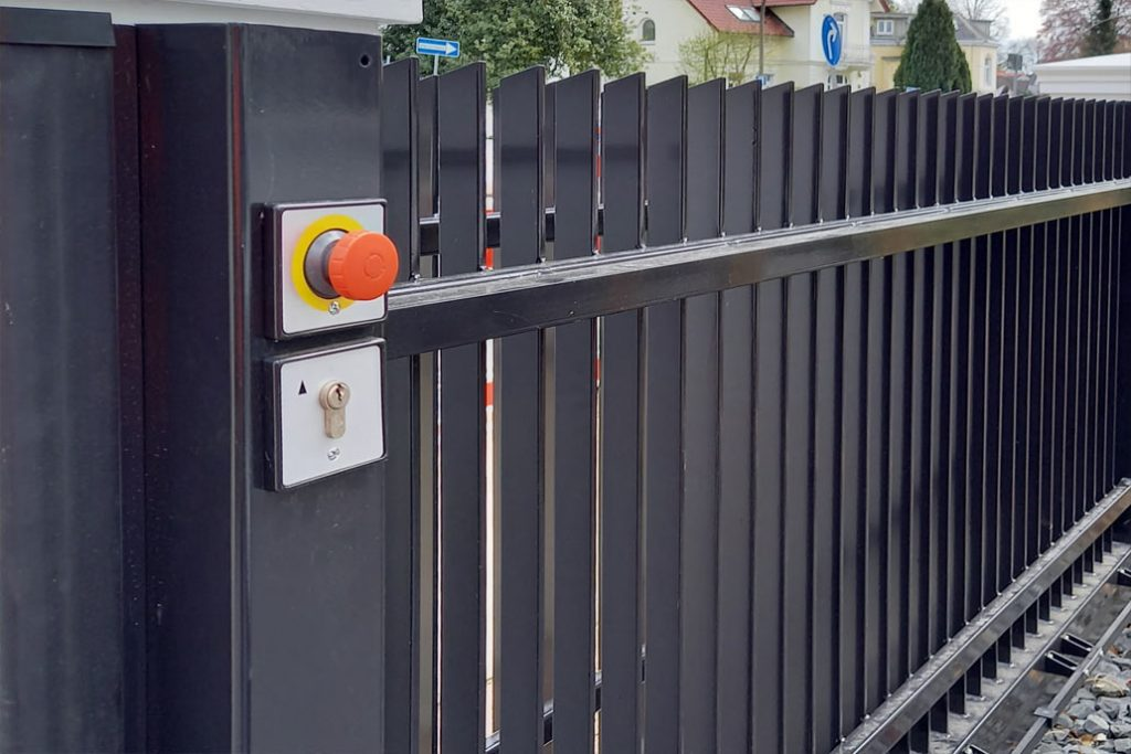 Ein knallroter Notstopp Knopf an einem kraftbetätigten Tor.