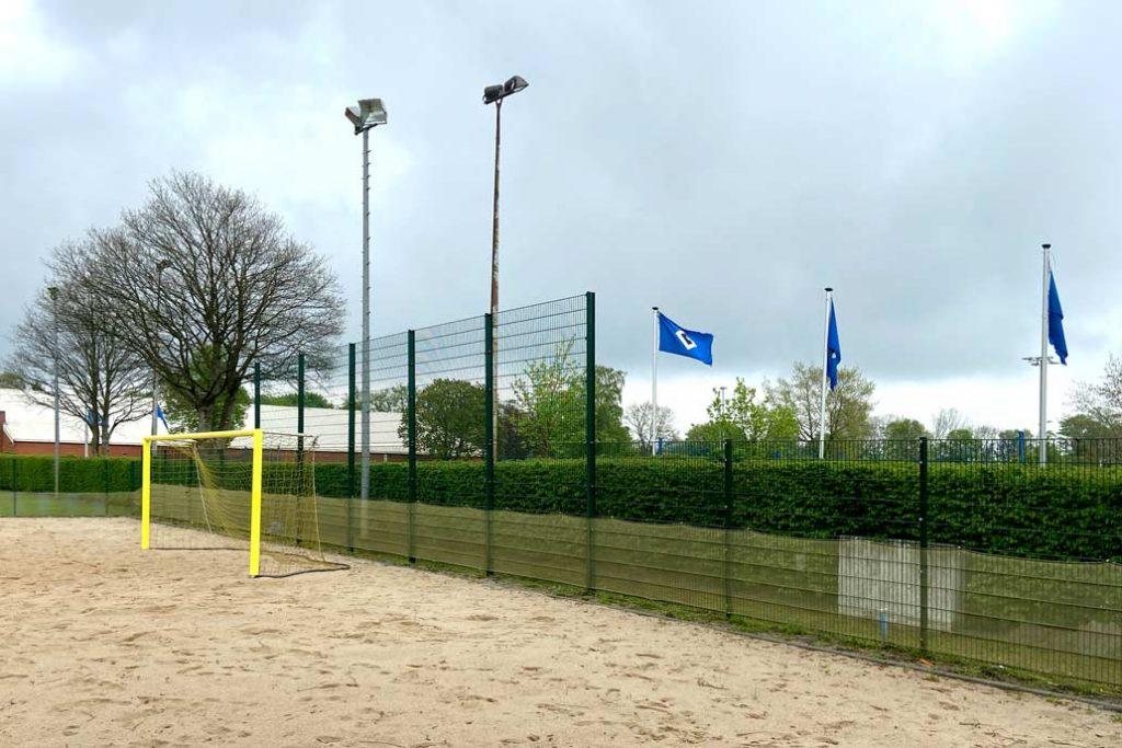 Ballfangzaun an einem Beachvolleyballfeld mit HSV Fahnen im Hintegrund.